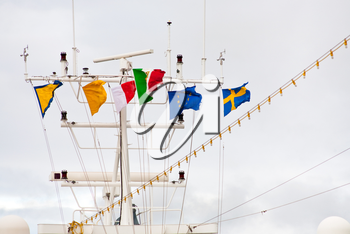 flags on navigation antenna of cruise liner