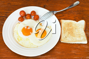 breakfast with two fried eggs on white plate, cherry tomatoes, fresh toast on wooden table