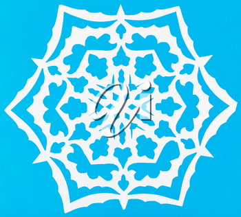 hand made cut out white snowflake on blue paper