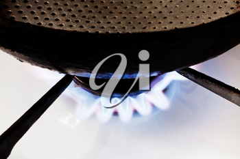 frying pan on burning gas in hearth ring of kitchen stove