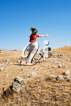 young woman jumping on Zorats Karer (Carahunge) plateau - pre-history megalithic monument in Armenia