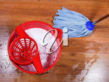 red bucket and mopping of wooden floors