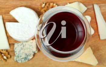 top view of glass of red wine and various cheeses on wooden plate close up