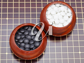set of black and white go game stones in wooden bowls