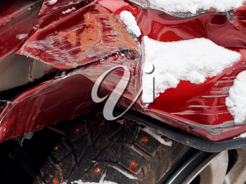 strongly crumpled fender of red car after winter traffic accident
