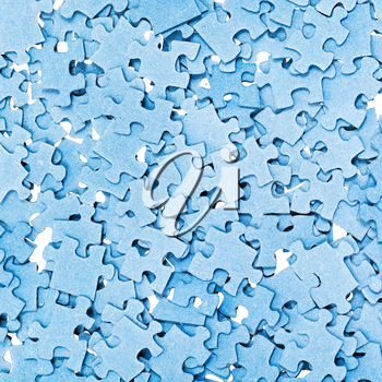 top view of many disassembled blue puzzle pieces