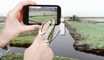 travel concept - tourist taking photo of frozen canals in Netherlands in winter on mobile gadget