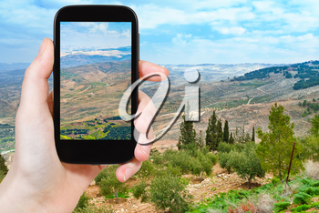 travel concept - tourist taking photo of Promised Land from Mount Nebo in Jordan on mobile gadget
