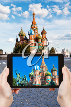 travel concept - tourist taking photo of Pokrovsky cathedral on Red square in Moscow on mobile gadget, Russia