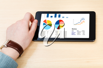 businessman hand hold tablet PC with business analytics on screen at office table