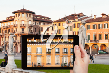 travel concept - tourist takes picture of facade of medieval house on piazza Prato della Valle in Padua in evening on tablet pc, Italy