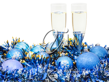 two glasses of sparkling wine at blue Christmas balls and tinsel isolated on white background