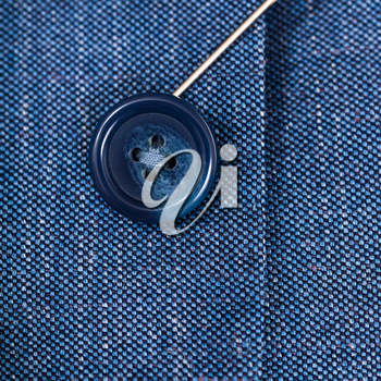 attaching of button to blue silk cloth by needle close up