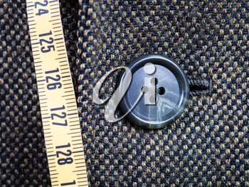 tailor measuring tape and buttoned button on tweed jacket close up