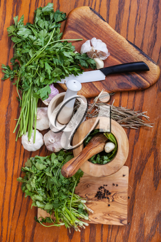 cooking seasonings - top view of mortars and fresh herbs on wooden table
