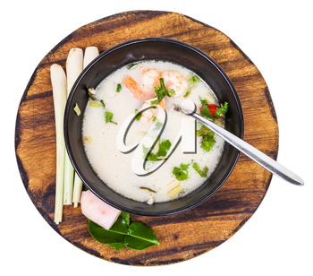top view soup Tom yam nam khon made with shrimps, coconut milk, chilli pepper, lemongrass, galangal, coriander, kaffir lime leaves in bowl and ingredients on wooden board isolated on white background