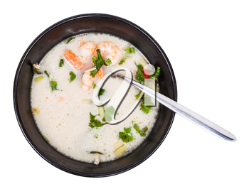 top view of sour and spicy soup Tom yam nam khon made with shrimps, coconut milk, chilli pepper, lemongrass, galangal, coriander, kaffir lime leaves in bowl isolated on white background