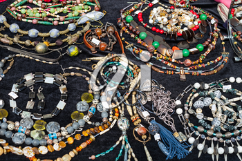 table with handmade necklaces from natural gemstones and jewelry at the fair
