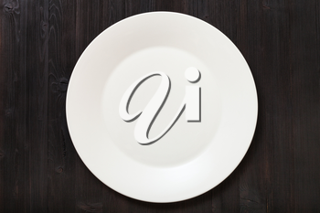 top view of one white plate on dark brown table