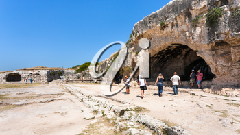 SYRACUSE, ITALY - JULY 3, 2011: tourists near artificial cave with nymphaeum of ancient Greek theater on Temenite Hill in Archaeological Park (Parco Archeologico della Neapolis) of Syracuse, Sicily