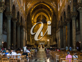 MONREALE, ITALY - JUNE 25, 2011: tourists indoor of Duomo di Monreale in Sicily. The cathedral of Monreale is one of the greatest examples of Norman architecture, it was begun in 1174
