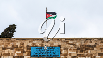 AMMAN, JORDAN - FEBRUARY 18, 2012: flag over Jordan Archaeological Museum at Amman Citadel in rainy day. Museum was built in 1951, it keeps artifacts from archaeological sites of Jordan
