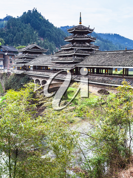 travel to China - covered Chengyang Wind and Rain Bridge over river (Fengyu Bridges of the Dong people) in Sanjiang Dong Autonomous County in spring season