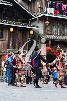 CHENGYANG, CHINA - MARCH 27, 2017: tourists and dong people in round dance on square of Folk Custom Centre during Culture Show in Chengyang village. Chengyang includes eight villages of Dong people