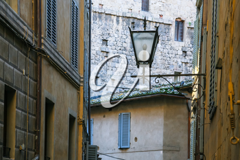 travel to Italy - lantern between medieval houses on street in Siena city in winter