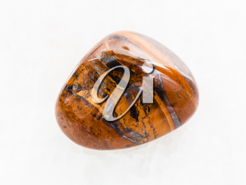 macro shooting of natural mineral rock specimen - polished tigers eye gemstone on white marble background