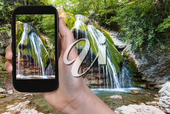 travel concept - tourist photographs Ulu-Uzen river with Djur-djur waterfall in Haphal Gorge of Habhal Hydrological Reserve natural park in Crimean Mountains in Crimea in september on smartphone