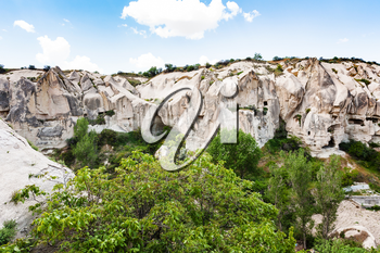 Travel to Turkey - walls of gorge with rock-cut ancient monastic settlement near Goreme town in Cappadocia in spring