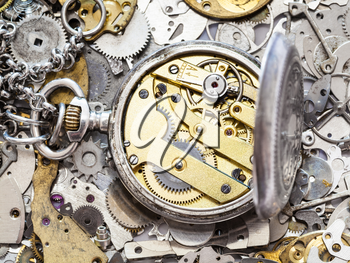 watchmaker workshop - open old silver pocket watch with brass clockwork on heap of clock spare parts