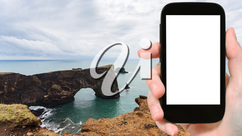 travel concept - tourist photographs stone arch on Dyrholaey cliff near Vik I Myrdal village in Iceland on Atlantic Coast in september on smartphone with cut out screen for advertising logo