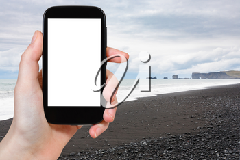 travel concept - tourist photographs Reynisfjara Beach and view of Dyrholaey promontory in Iceland on Atlantic South Coast in autumn on smartphone with cut out screen for advertising logo