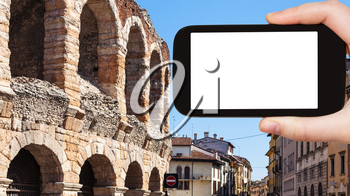 travel concept - tourist photographs Arena di Verona ancient Roman Amphitheatre in Verona city on smartphone with cut out screen for advertising logo