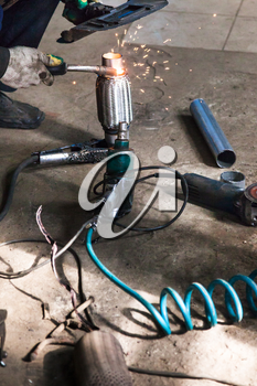 repairing of corrugation muffler of exhaust system in car workshop - mechanic fixes the pipe on corrugation silencer by argon welding