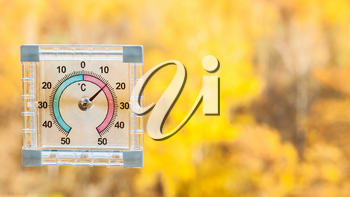 outdoor thermometer on home window and blurred yellow forest on background in sunny warm autumn day