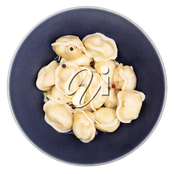 top view of boiled Pelmeni (russian dumplings filled with minced meat) with butter and peppercorn in black bowl isolated on white background