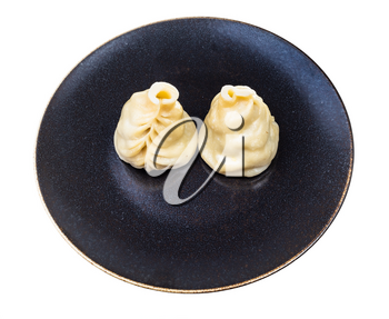 two cooked Buuz (Mongolian dumpling filled with minced meat) on dark brown plate isolated on white background