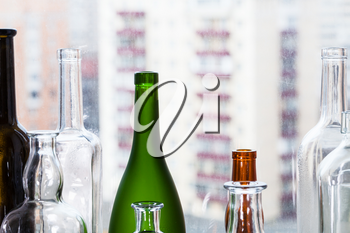 many empty bottles and view of apartment buildings through home window on background
