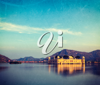Vintage retro hipster style travel image of Rajasthan landmark - Jal Mahal (Water Palace) on Man Sagar Lake on sunset with grunge texture overlaid.  Jaipur, Rajasthan, India