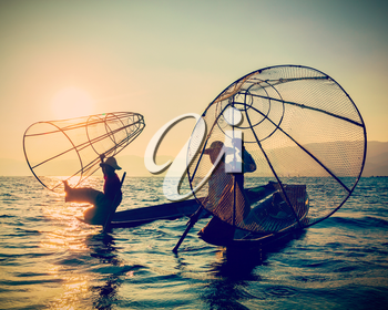 Myanmar travel toursist attraction landmark - two traditional Burmese fishermen at Inle lake, Myanmar on sunrise. Vintage filtered retro effect hipster style image