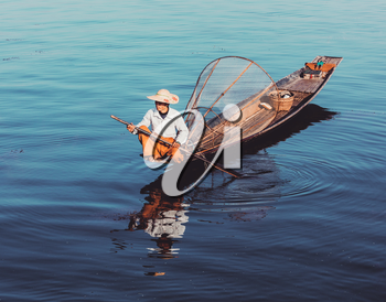 Myanmar travel attraction - Traditional Burmese fisherman at Inle lake, Myanmar famous for their distinctive one legged rowing style. Vintage filtered retro effect hipster style image