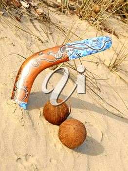 Colorful boomerang and two coconuts on a sand.