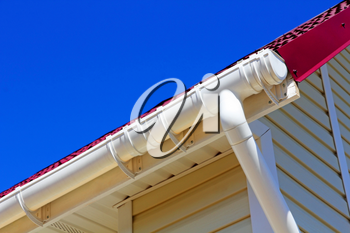 New plastic rain gutter system with drainpipe against blue sky.