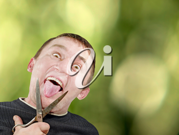 Mad man with scissors cuts off itself tongue on green abstract background.
