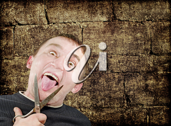 Mad man with scissors cuts off itself tongue on grunge brick wall background.
