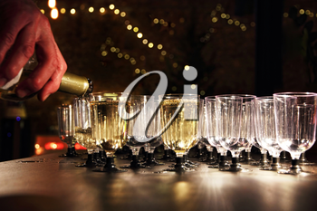 Waiter pour wine in the glass on holiday reception table in night-time lighting.