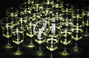 White sparkling wine in glasses on holiday reception table at nightclub.Toned image.